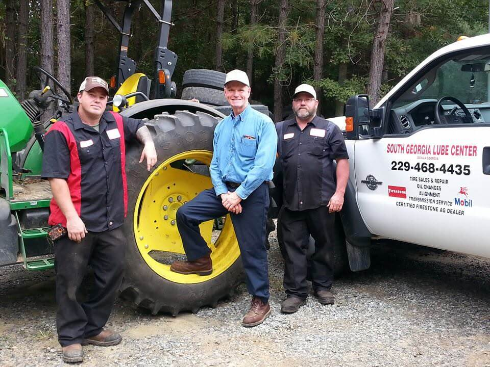 Picture of three team members and one of the roadside assistance trucks from South Georgia Lube Center's Facebook Page